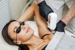 Beautician stosuje włosianą usunięcia lub laseru epilację w pachy strefie zdjęcia royalty free
