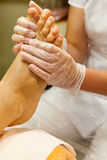 Beautician taking care of female client's foot giving pedicure - hand massage with scrub. Stock Image
