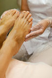 Beautician taking care of female client's foot giving pedicure treatment. Stock Image