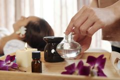Beautician taking massage oil. Beautician taking professional scented massage oil for face massage stock image