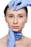 Beautician touch and exam health woman face. Royalty Free Stock Images