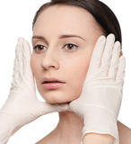 Beautician touch and exam health woman face. Stock Images