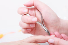 Beautician trimming cuticles of female client in beauty salon Royalty Free Stock Images