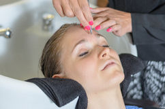 Beautician trimming a young girls eyebrows Royalty Free Stock Images