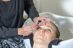 Beautician trimming a young girls eyebrows Stock Photography