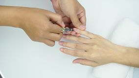 Beautician use clipper cleaning and cutting cuticle at nail and spa salon. Woman receiving fingernail manicure service stock footage
