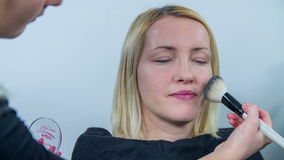 Beautician using the brash. Slow motion close up RAW footage of a woman getting her make up done by a  using the brash to puff her face stock video