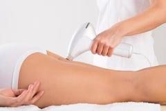 Beautician Using Laser Machine On Young Customer& x27;s Leg Stock Photos