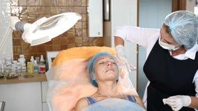 Beautician w opieki zdrowotnej klinice Stosuje anestezję przed twarzową procedurą Starsza kobieta dostaje piękna traktowanie 4K zbiory wideo