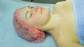 Beautician w rękawiczkach z muśnięciem stosuje błoto maskę na kobiety twarzy zbiory