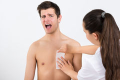 Beautician Waxing Man's Chest In Beauty Center. Female Beautician Waxing Man's Chest With Wax Strip In Beauty Center Royalty Free Stock Images