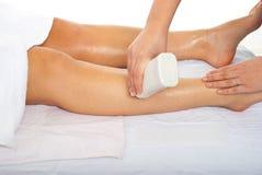 Beautician waxing woman leg. Beautician waxing woman's leg at spa salon Royalty Free Stock Photos