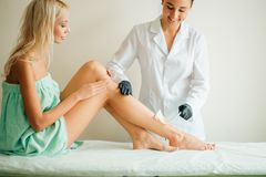 Beautician waxing woman leg with depilation strip at salon. Beautician waxing a woman`s leg applying a strip of material over the hot wax to remove the hairs Stock Images