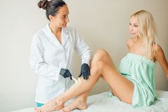 Beautician waxing woman a leg at salon. Depilation. Beautician waxing female legs in spa center Royalty Free Stock Photo