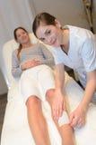 Beautician waxing woman leg at salon Royalty Free Stock Photos