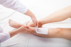 Beautician waxing  woman legs in spa salon Stock Photography