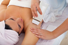 Beautician waxing woman's armpit. At spa salon Stock Photography