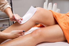 Beautician waxing a woman's leg. Applying a strip of material over the hot wax to remove the hairs Stock Image