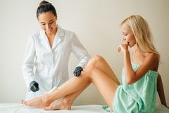 Beautician waxing woman leg with depilation strip at salon. Beautician waxing a woman`s leg applying a strip of material over the hot wax to remove the hairs Royalty Free Stock Photos