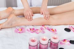 Beautician waxing woman's leg. Applying Wax Strip Royalty Free Stock Images