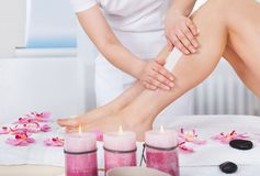 Beautician waxing woman's leg Stock Photography