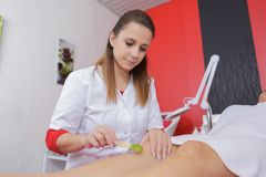 Beautician waxing womans leg Royalty Free Stock Photo