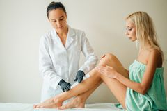 Beautician waxing a woman leg applying a strip of material over the hot wax. Beautician waxing women leg with depilation strip at salon Stock Photos