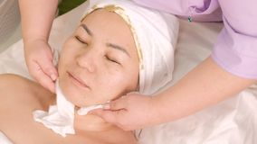 The beautician wipes the skin and cleans the remains of the cosmetic mask from algae on the neck and face of an Asian girl. Close-. Up of female hands and face stock footage
