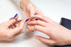 Beautician work with nail scissors ring finger Stock Photography