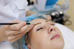 Beautician that works with eyebrow of woman. Royalty Free Stock Photo