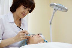 Beautician works with eyebrow of woman. Stock Photography