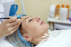 Beautician works with eyebrow of woman Royalty Free Stock Photo