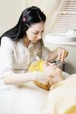 Beauticianen gör dragning av hårborttagning Royaltyfri Fotografi
