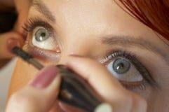 beauticianen som gör den haired flickan, gör red till upp Fotografering för Bildbyråer