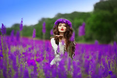 Beautidul brunette teen girl sends an air kiss over wild flowers. Field nature background. Attractive young woman with wheat on head, long curly hair Royalty Free Stock Image