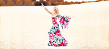 Beautidul smiling lady dancing Belly dance in the sands desert. Royalty Free Stock Photos