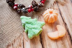 Beautiful handmade green soap Christmas tree and mandarin on a wooden background concept of happy christmas and new year stock photo