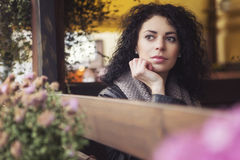 Beautifil brunette caucasian woman in leather jacket sitting on Royalty Free Stock Photography