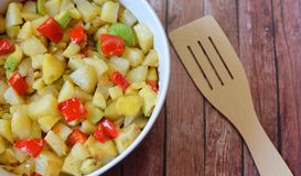 Beautifil fried potatoes with vegetables. Beautifil dish fried potatoes with vegetables on the wooden background Stock Images