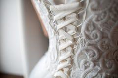 Beautifil drar tillbaka den vita bröllopsklänningen på brudar arkivbild