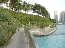 A beautifil view if Dubai. A typical view of pathway leading to the Dubai Mall and Burj Khalifa. Nice garden on one side and water lake on the other side Royalty Free Stock Photo