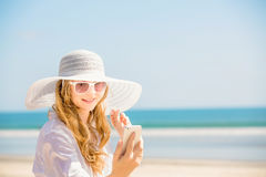 Beautifil young woman sitting on the beach at Royalty Free Stock Photography