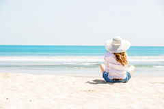 Beautifil young woman sitting on the beach at Stock Image