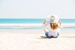 Beautifil young woman sitting on the beach at Royalty Free Stock Images
