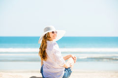 Beautifil young woman sitting on the beach at Stock Images