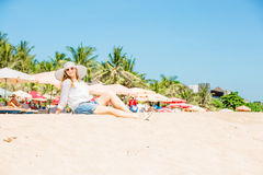 Beautifil young woman sitting on the beach at Royalty Free Stock Image