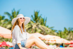 Beautifil young woman sitting on the beach at Royalty Free Stock Photo