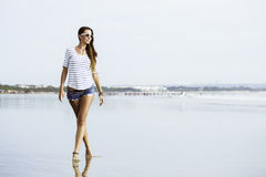 Beautifil young woman with walking along the beach Stock Image