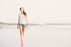 Beautifil young woman walking along the beach at Royalty Free Stock Photography