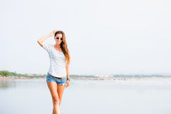 Beautifil young woman walking along the beach at Stock Photo